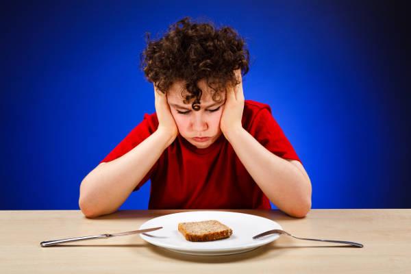 dítě sedí u stolu s jídlem a nemá hlad