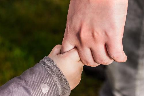 dětská ruka se drží prstu rodiče