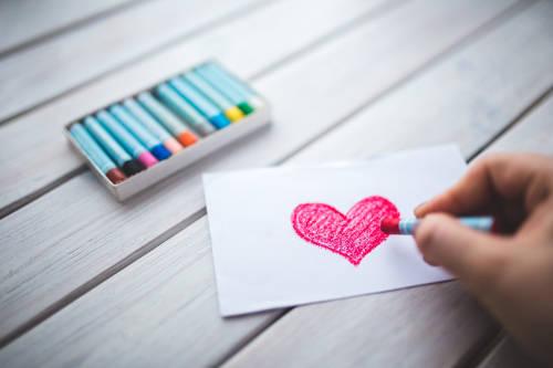 dítě maluje srdíčko voskovkami